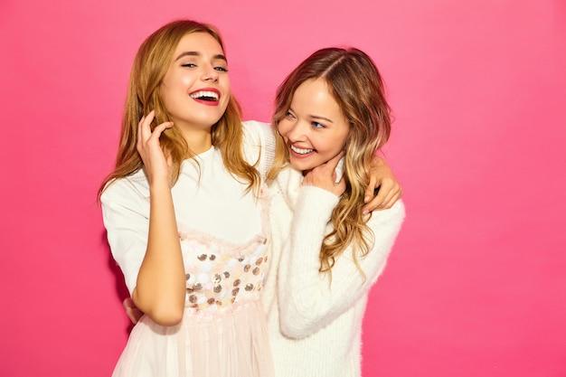 Duas jovens lindas mulheres sorridentes em roupas da moda verão branco
