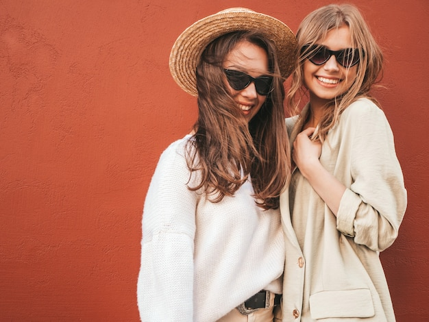 Duas jovens lindas sorrindo hippie feminino com casaco e suéter branco da moda