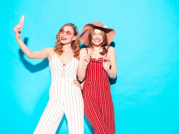 Duas jovens lindas sorrindo hippie feminino com roupas da moda de macacão de verão