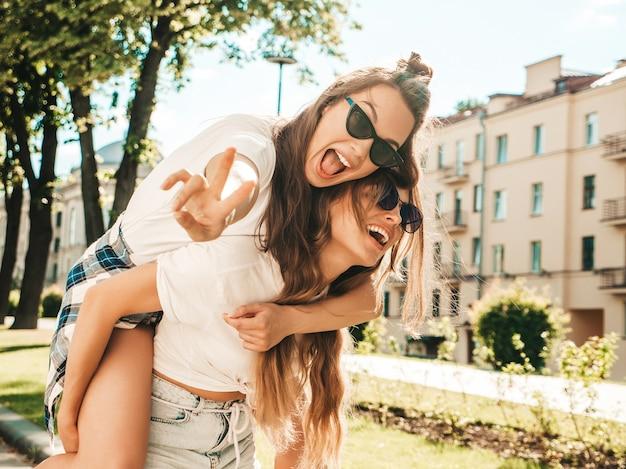 Duas jovens lindas sorrindo hipster com roupas da moda de verão branco