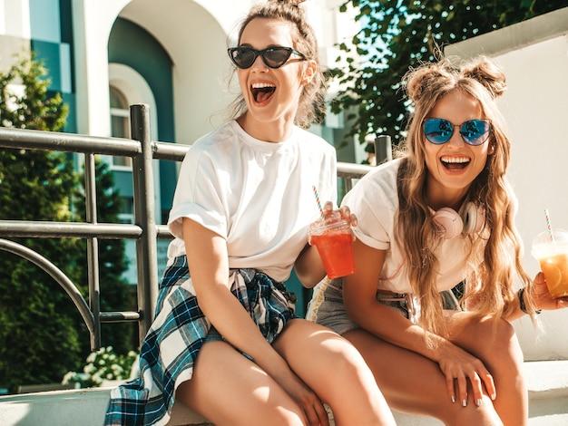 Duas jovens lindas sorrindo hipster com roupas da moda de verão