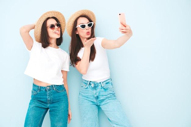 Duas jovens lindas sorrindo hipster com roupas jeans e camiseta branca na moda do mesmo verão