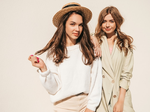 Duas jovens lindas sorrindo hipster feminina com casaco e suéter branco da moda