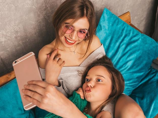 Duas jovens lindas sorrindo lindas garotas em roupas da moda no verão. mulheres despreocupadas sexy, posando no interior e tomar selfie. modelos positivos se divertindo com o smartphone.