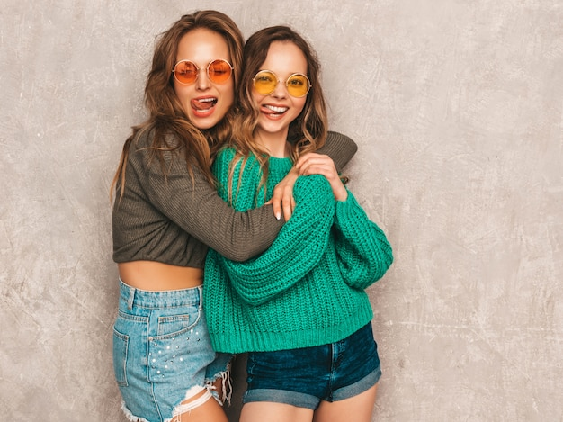 Duas jovens lindas sorrindo lindas garotas em roupas da moda no verão. mulheres sexy despreocupadas posando. modelos positivos se divertindo em óculos de sol redondos. mostrando a língua