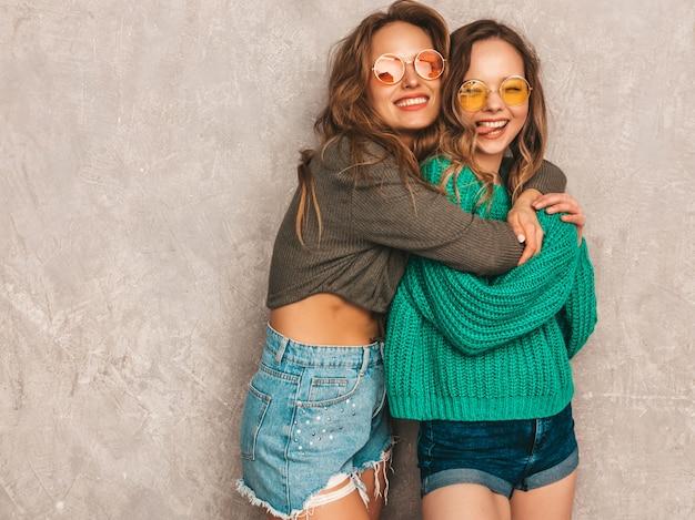 Duas jovens lindas sorrindo lindas garotas em roupas da moda no verão. mulheres sexy despreocupadas posando. modelos positivos se divertindo em óculos de sol redondos
