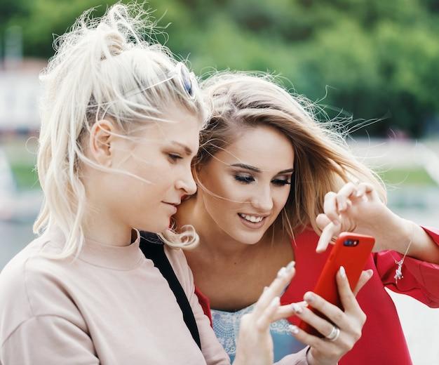 Duas jovens loiras escolhem algo no telefone