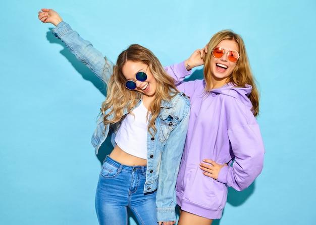 Duas jovens loiras lindas hipster mulheres sorridentes em roupas da moda no verão. mulheres despreocupadas