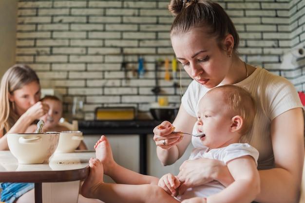 Duas jovens mães alimentam seus bebês felizes com mingau de leite na cozinha