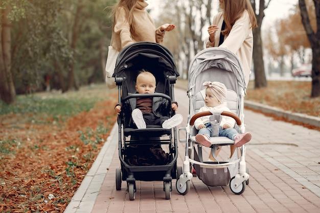 Duas jovens mães andando em um parque de outono com carruagens