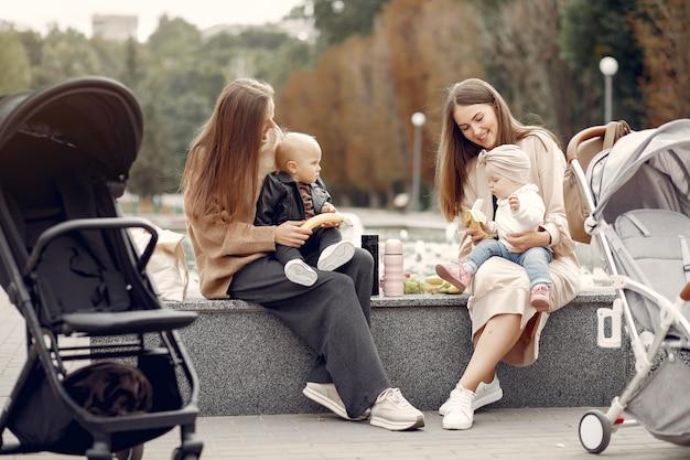 Duas jovens mães sentadas em um parque de outono com carruagens