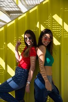 Duas jovens melhores amigas em pé junto à parede amarela