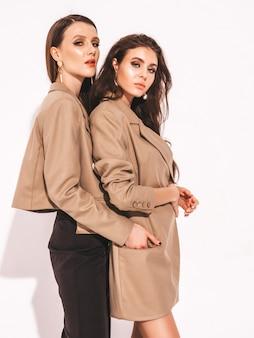 Duas jovens meninas morenas lindas no verão na moda agradável semelhante combina com roupas