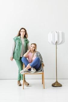 Duas jovens modelos femininas posando com roupas da moda casuais