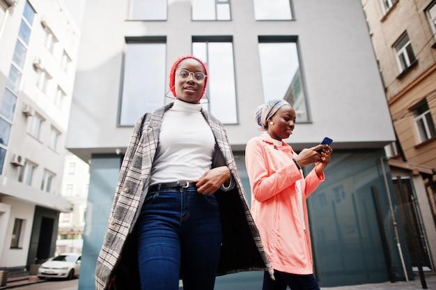 Duas jovens modernas, elegantes, atraentes, altas e magras, de hijab e casaco, com telefones celulares