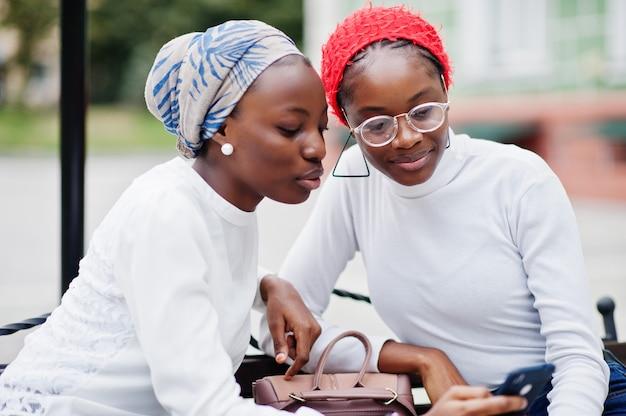 Duas jovens modernas, elegantes, atraentes, altas e magras no hijab, colocadas junto com os telefones celulares nas mãos