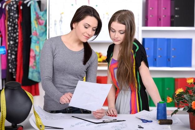 Duas jovens mulheres alegres que trabalham no design de moda.