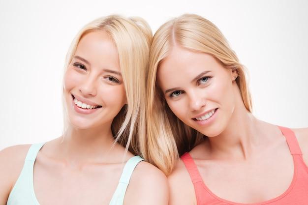 Duas jovens mulheres alegres vestidas com camisetas posando. isolado sobre parede branca