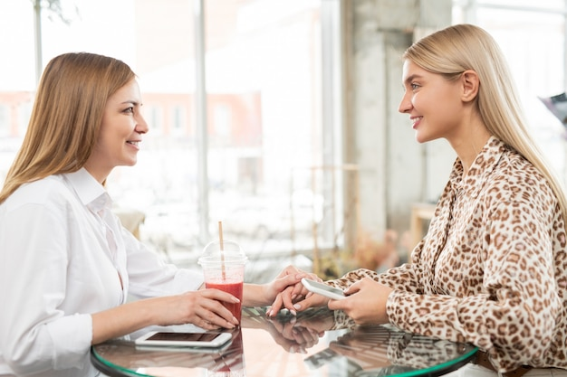 Duas jovens mulheres amigáveis em trajes casuais elegantes, sentadas no café do shopping depois de fazer compras, tomando drinques e discutindo notícias