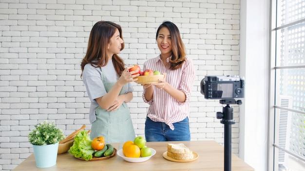 Duas jovens mulheres asiáticas blogueiros de comida falando enquanto gravava vídeo com o momento feliz