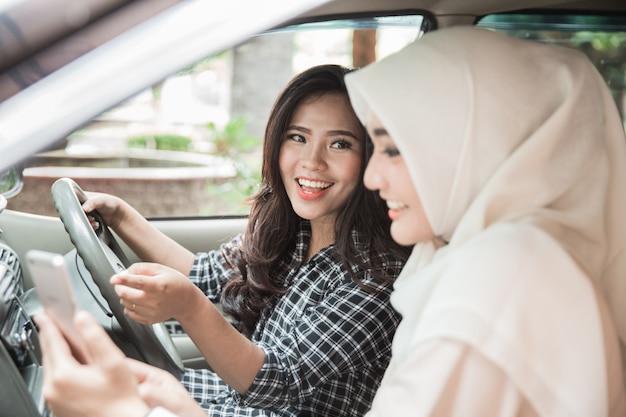 Duas jovens mulheres asiáticas no carro