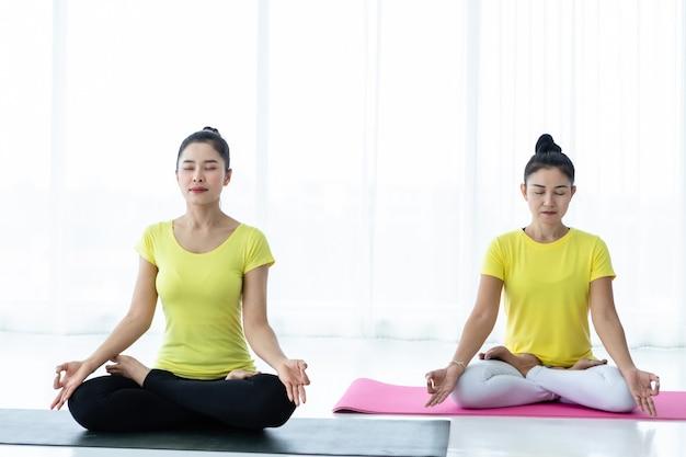 Duas jovens mulheres asiáticas treino praticando ioga em vestido amarelo ou pose com um treinador e prática de meditação bem-estar estilo de vida e conceito de fitness de saúde em um ginásio.