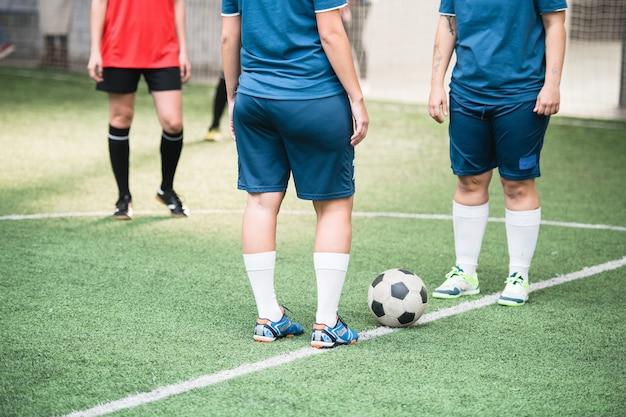 Duas jovens mulheres ativas com uniforme esportivo azul paradas uma frente à outra com uma bola de futebol entre elas na linha branca
