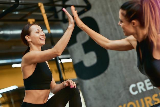 Duas jovens mulheres atléticas felizes em roupas esportivas, dando mais cinco uns aos outros durante o exercício juntos no ginásio. esporte, treinamento, bem-estar e estilo de vida saudável