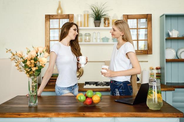 Duas jovens mulheres atraentes em pé atrás da mesa da cozinha, bebendo chá e conversando