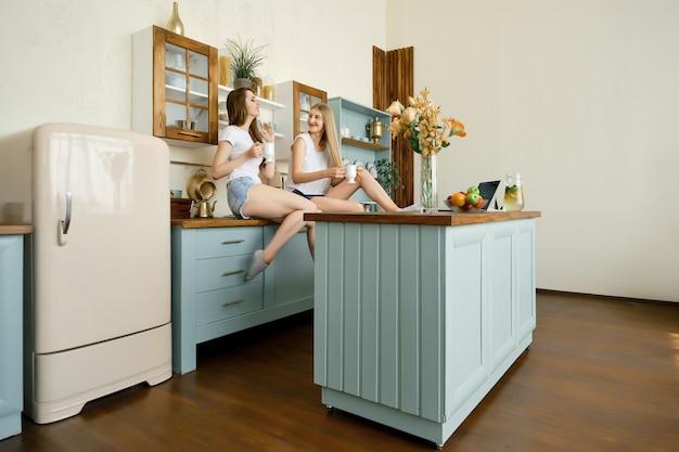 Duas jovens mulheres atraentes tomando chá e conversando na cozinha