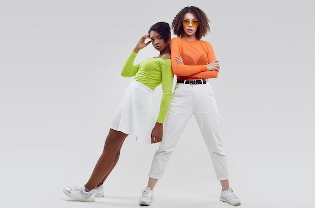 Duas jovens mulheres bonitas em roupas coloridas do verão