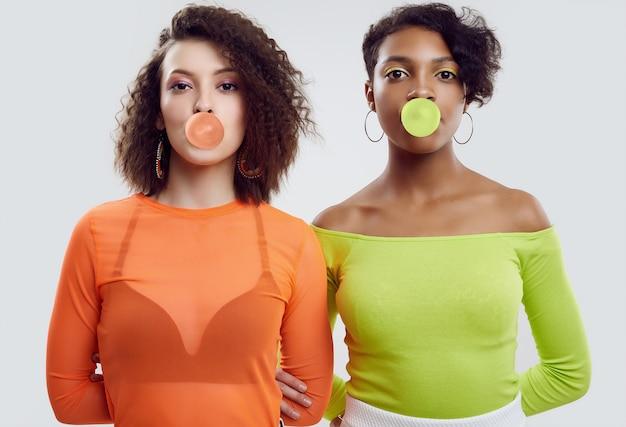 Duas jovens mulheres bonitas em roupas coloridas, soprando bolhas de chiclete