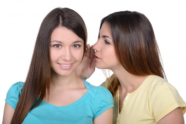 Duas jovens mulheres bonitas que bisbilhotam em casa.