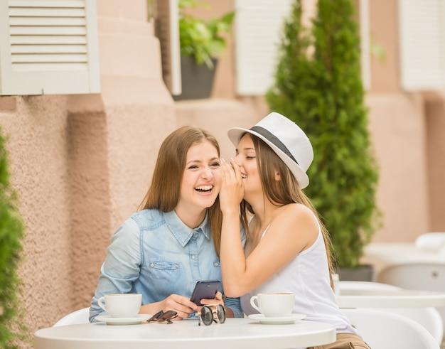 Duas jovens mulheres bonitas que sentam-se no café do verão.