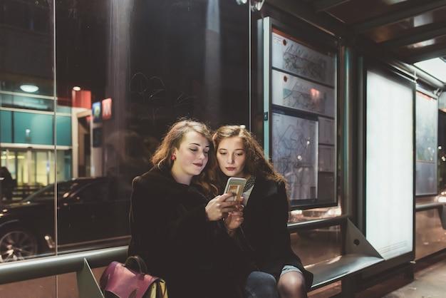 Duas jovens mulheres bonitas sentado ponto de ônibus usando o telefone