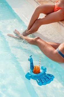 Duas jovens mulheres brancas em trajes de banho relaxando com coquetéis tropicais perto de uma piscina