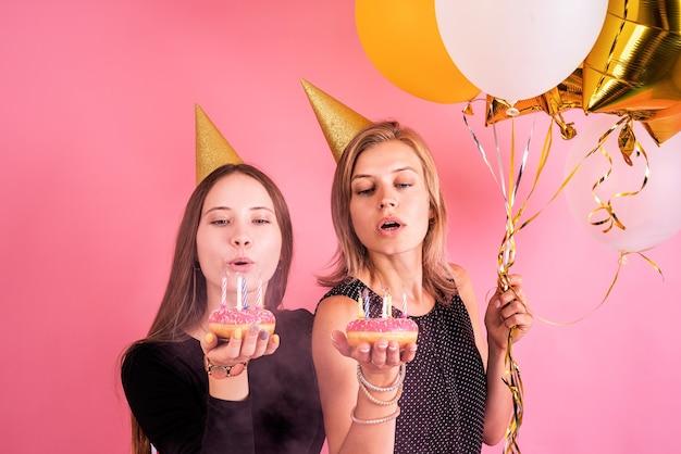 Duas jovens mulheres com chapéus de aniversário segurando balões comemorando o aniversário, segurando donuts com velas sobre fundo rosa