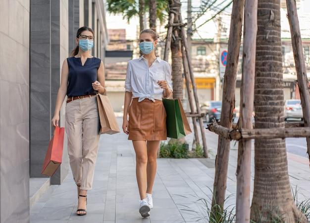 Duas jovens mulheres com máscara médica protetora carregam sacolas de compras caminhando ao ar livre na rua em um shopping center