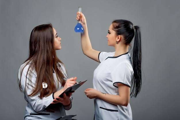 Duas jovens mulheres de cabelos compridos concentradas olhando um frasco com líquido azul isolado na sala.