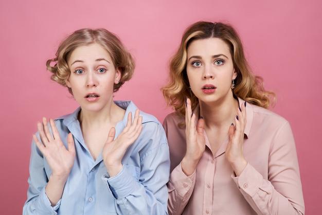 Duas jovens mulheres de pele branca ficam surpresas com o incidente e abrem a boca com as mãos. conceito de surpresa e choque