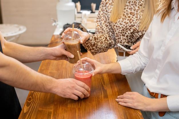 Duas jovens mulheres elegantes comprando bebidas no refeitório depois de fazer compras em um moderno centro comercial ou shopping e indo para o intervalo