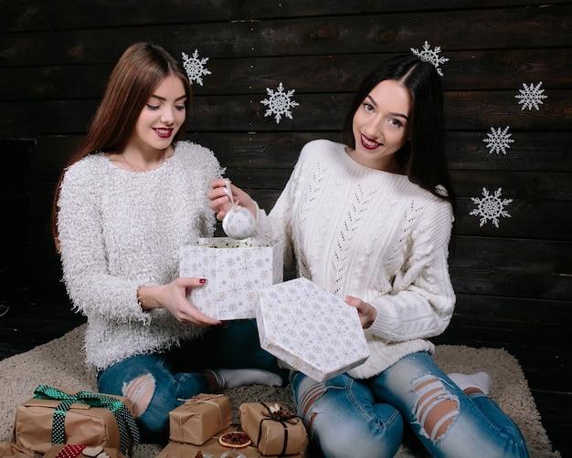 Duas jovens mulheres engraçadas amigas sorrindo e se divertindo, segurando o feriado apresenta, prontos para a celebração.