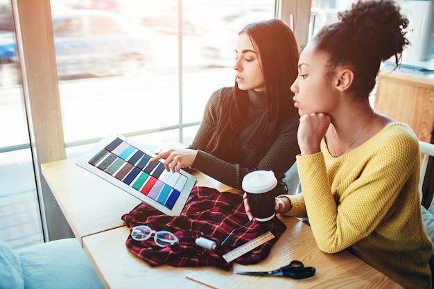 Duas jovens mulheres juntas e trabalhando para o mesmo projeto de moda.