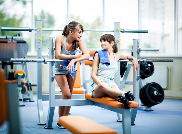 Duas jovens mulheres magras bonitas no sportswear cinza com toalhas com garrafa de água e olhando um ao outro no ginásio