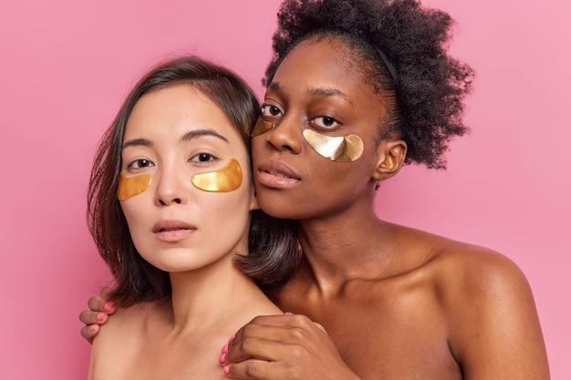 Duas jovens mulheres multiétnicas aplicam manchas douradas sob os olhos, mantendo-se próximas uma da outra, para ter uma pele saudável, limpa e macia, aproveite o spa e o dia da beleza isolado na parede rosa