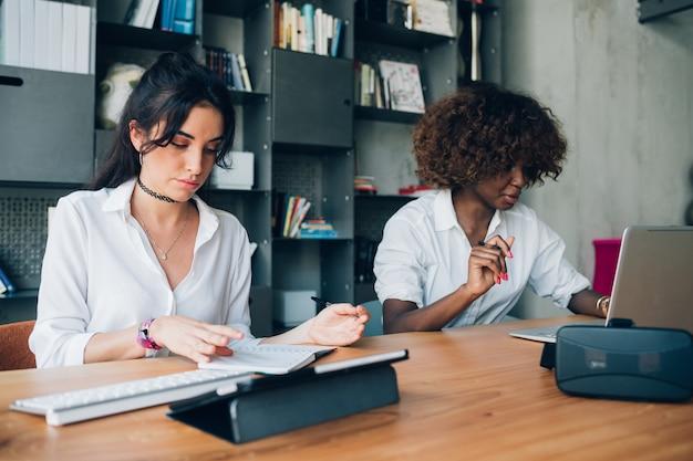 Duas jovens mulheres multirraciais trabalhando em um projeto em um escritório de coworking