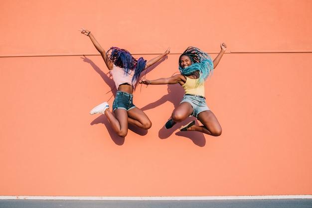 Duas jovens mulheres negras pulando ao ar livre espalhando braços se divertindo