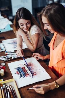Duas jovens mulheres que frequentam aulas de pintura aquarelle para adultos na escola de arte
