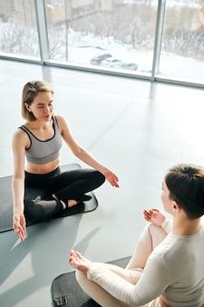 Duas jovens mulheres relaxadas em roupas esportivas sentadas em colchonetes em frente uma da outra em pose de lótus enquanto praticam ioga na academia