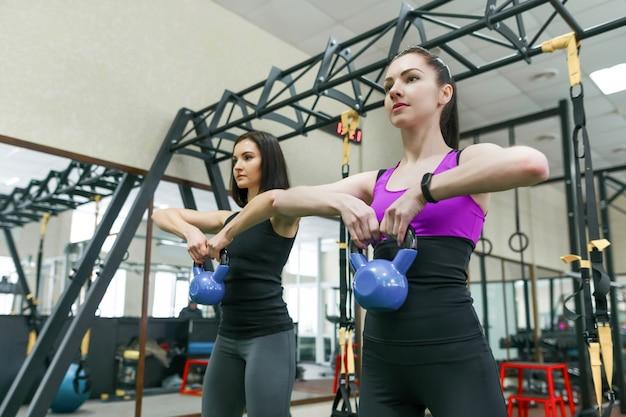 Duas jovens mulheres saudáveis fazendo exercícios com peso